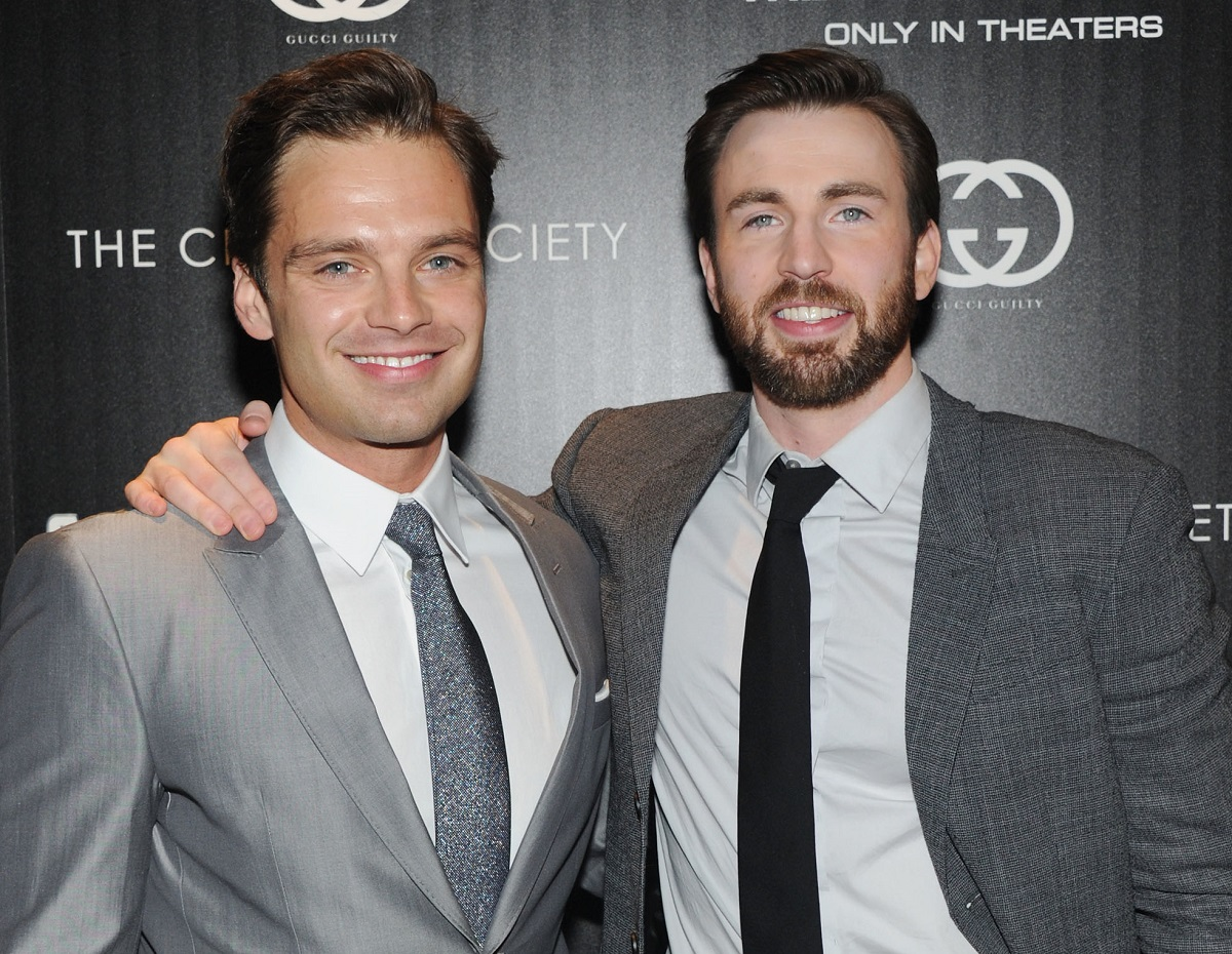 Chris Evans (R) with his arm around Sebastian Stan, both in gray suits