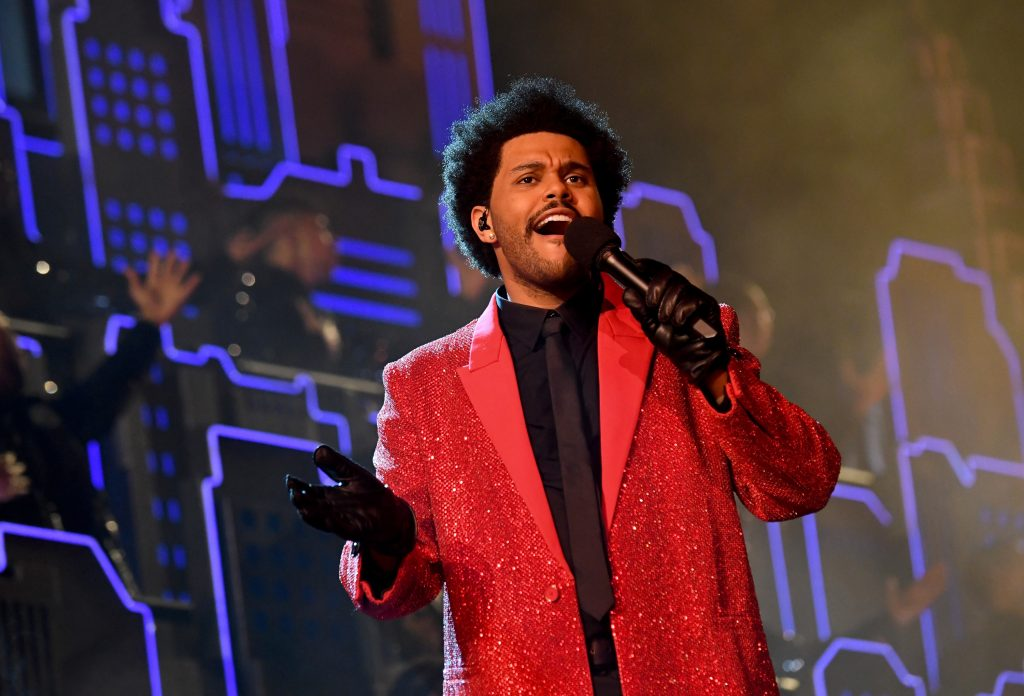 The Weeknd holds a microphone singing in a red jacket and black gloves at the Super Bowl halftime show
