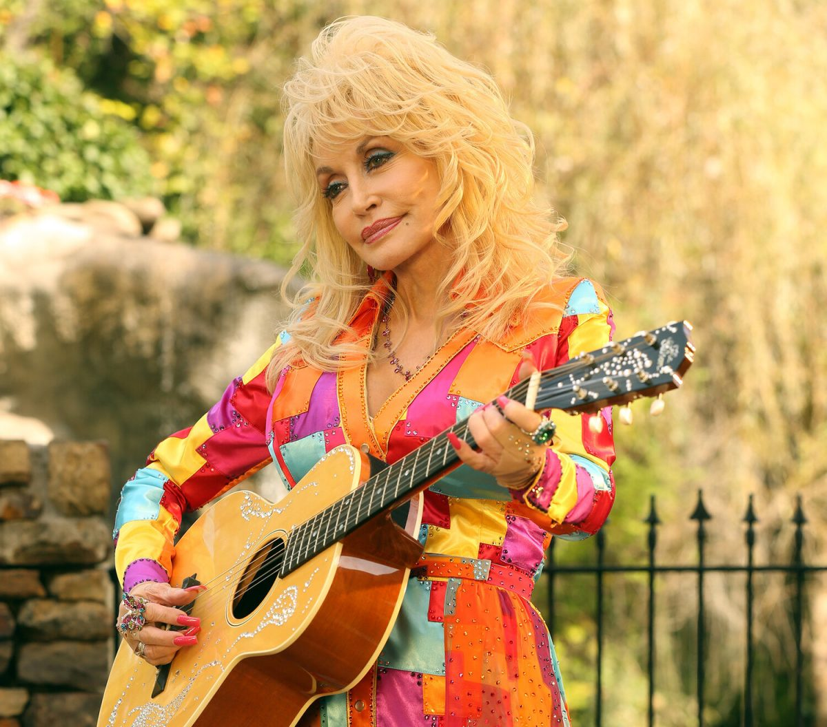 Dolly Parton plays the guitar in a coat-of-many-colors-inspired dress.