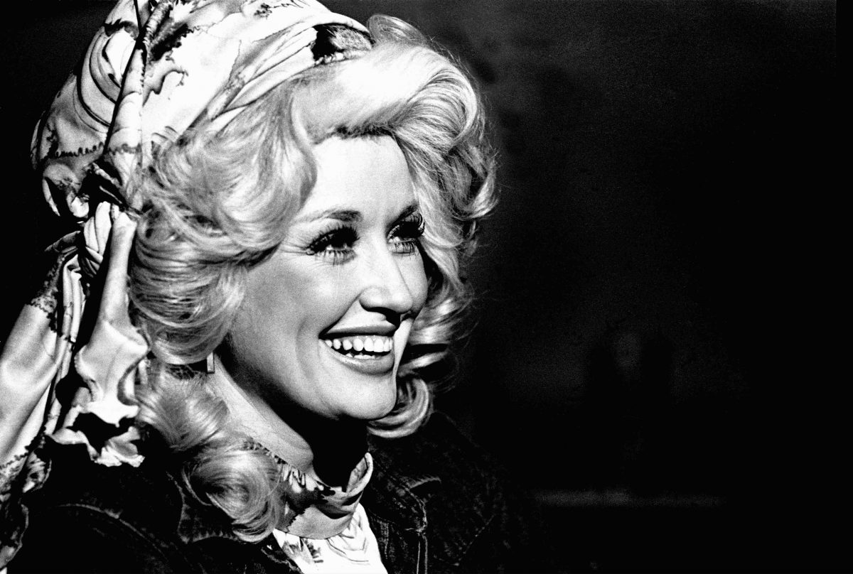 A close-up of Dolly Parton smiling her famous smile in black and white. Her hair is big and curly in a beehive with a scarf fastened around her head. The photo was taken in 1978.