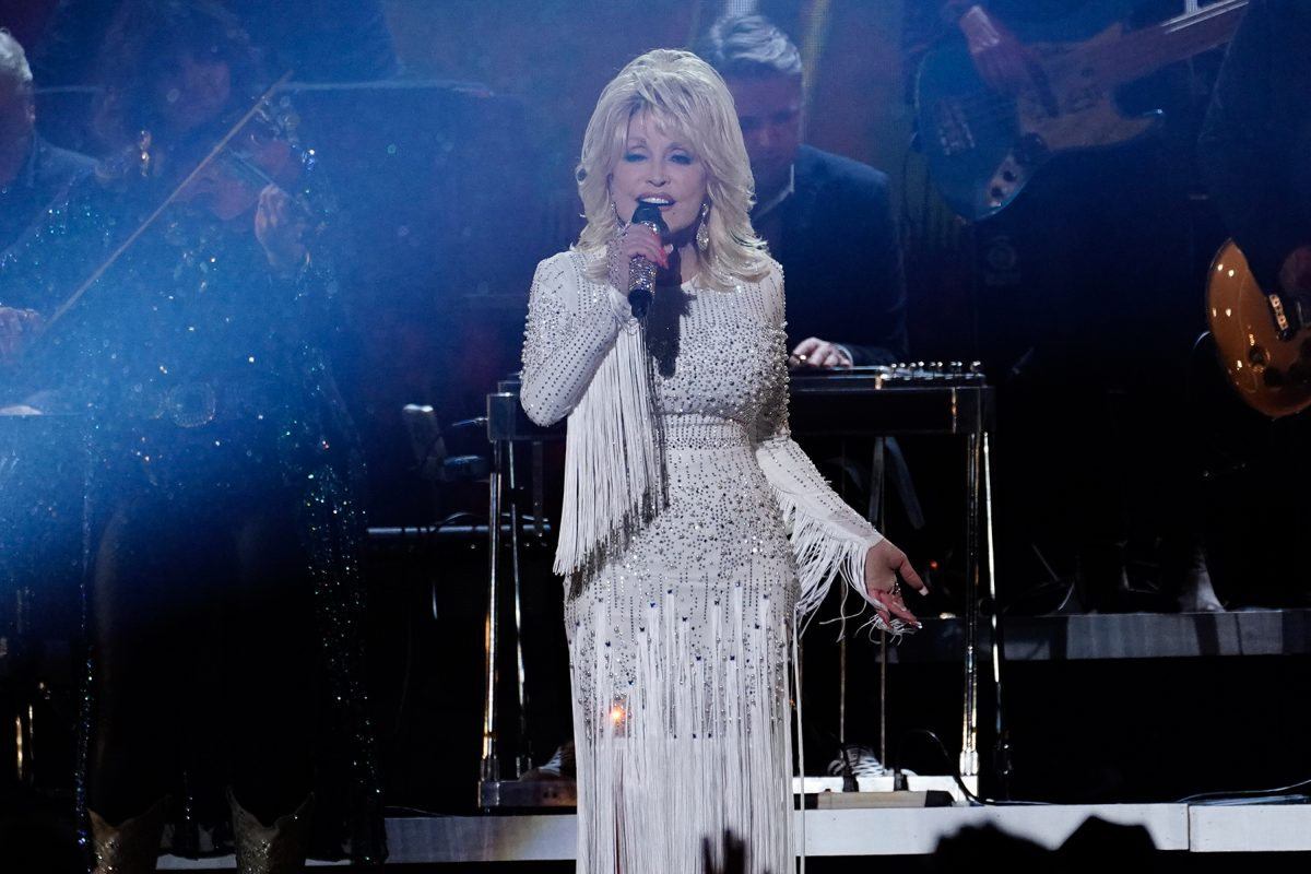 Dolly Parton at the 53rd annual CMA Awards at the Bridgestone Arena on November 13, 2019 in Nashville, Tennessee. She's in a long white dress with fringe on the sleeves, singing into a microphone with a band behind her.