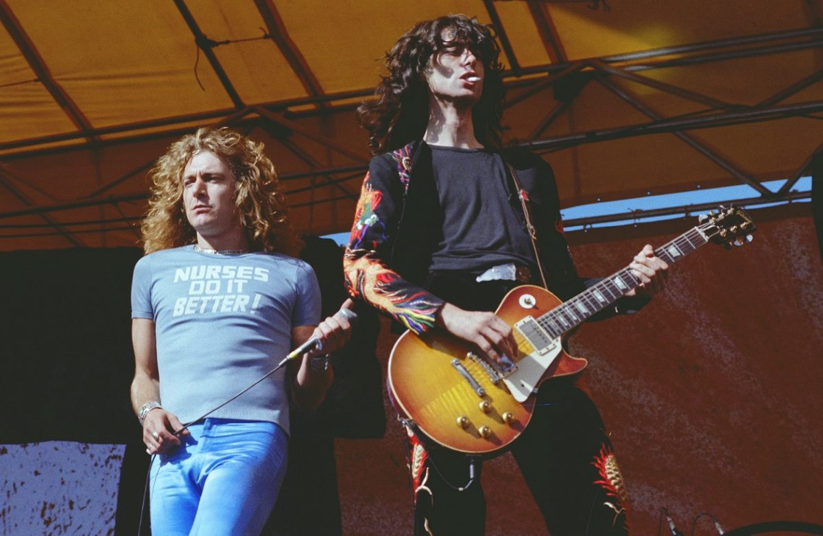 Robert Plant holds a microphone while Jimmy Page plays guitar at a Led Zeppelin concert