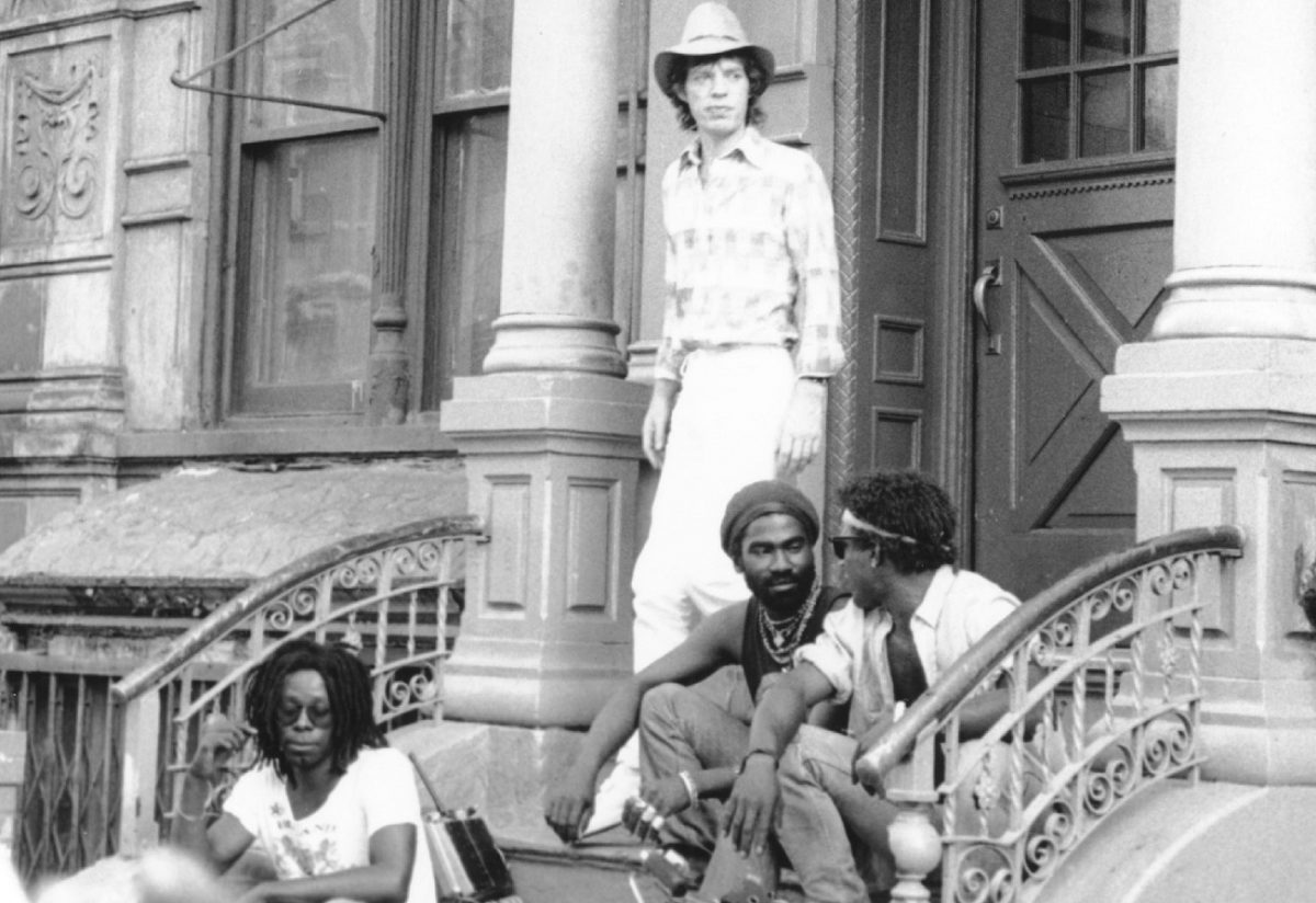 Mick Jagger stands on the stoop of a New York building while shooting a music video