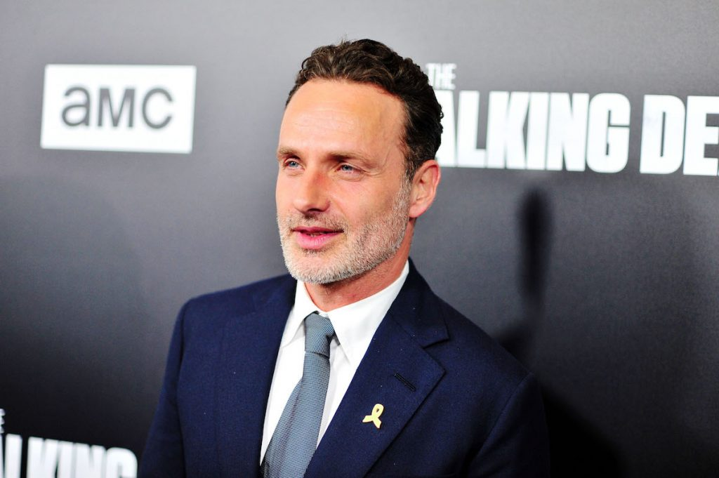 Andrew Lincoln poses in a blue suit and tie on the red carpet.