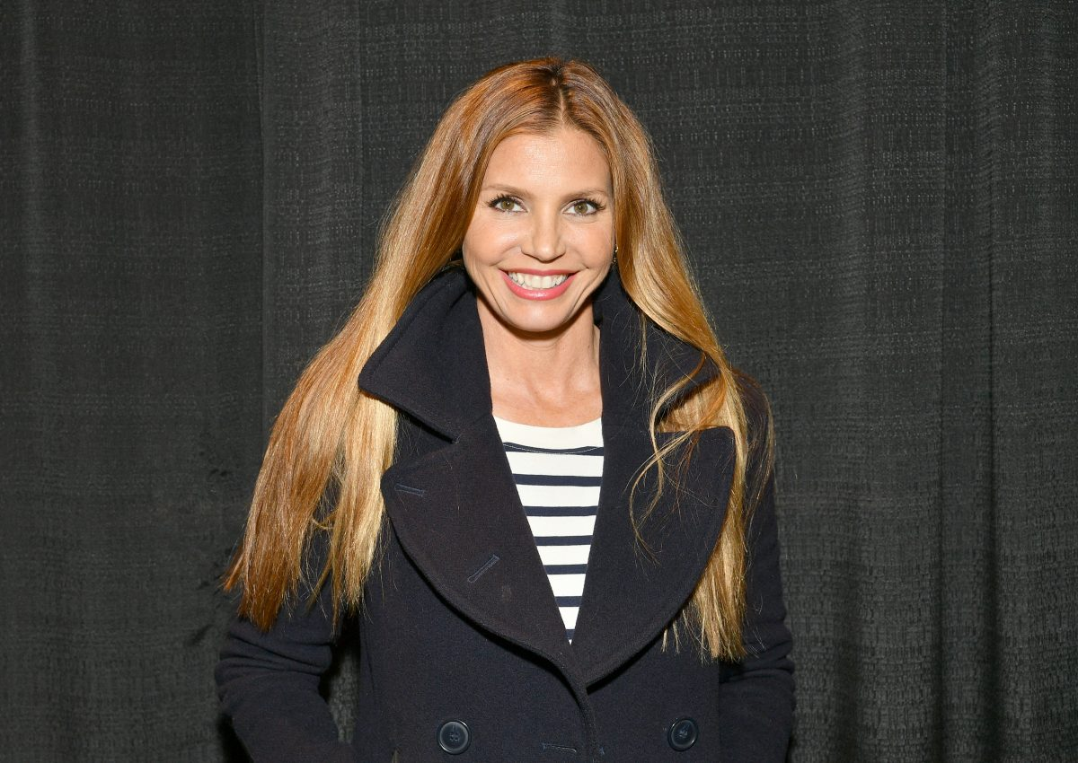Charisma Carpenter wears a black coat with her hair draped around the collar