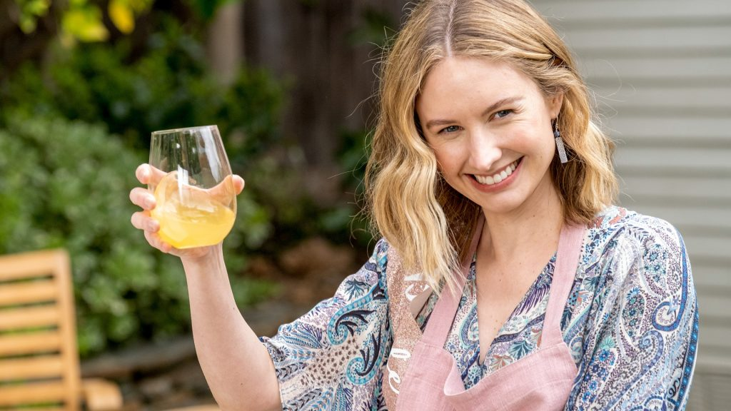 Caitlin Thompson lifts a glass of lemonade as Madison in 'This Is Us' Season 5 Episode 15, 'Jerry 2.0'