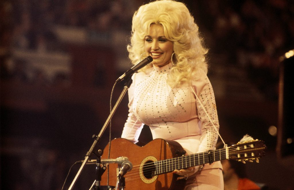 Dolly Parton performs with a guitar on stage in 1976.