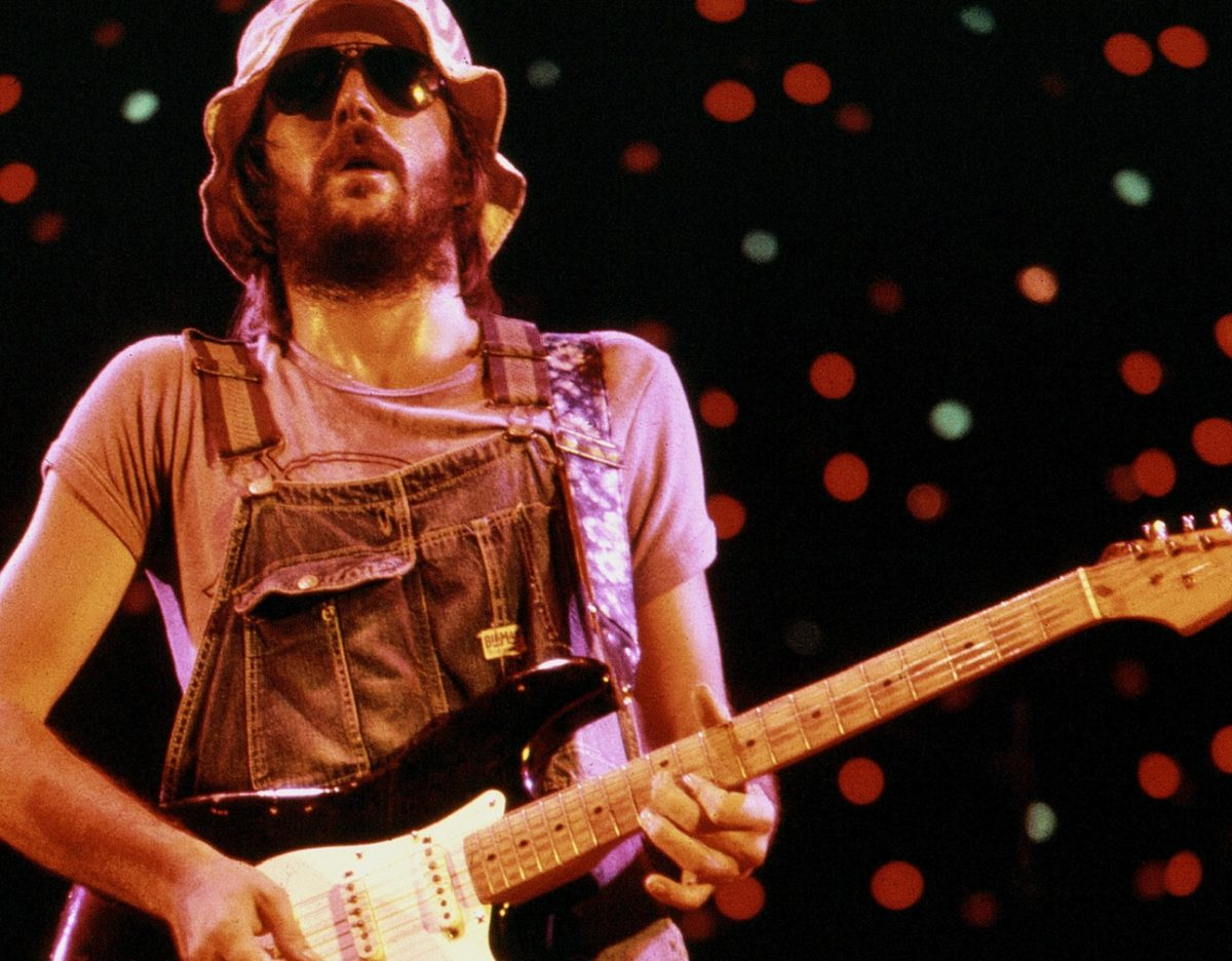 Eric Clapton plays guitar wearing overalls and sunglasses on stage in 1974