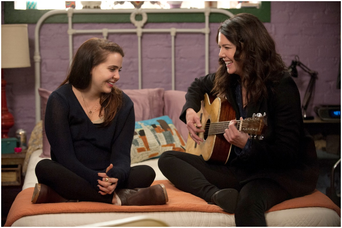 Mae Whitman and Lauren Graham sitting on a bed while smiling as Amber Holt and Sarah Braverman on 'Parenthood'