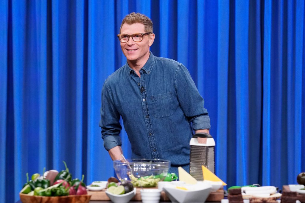 Chef Bobby Flay smiles in front of a counter of food prep