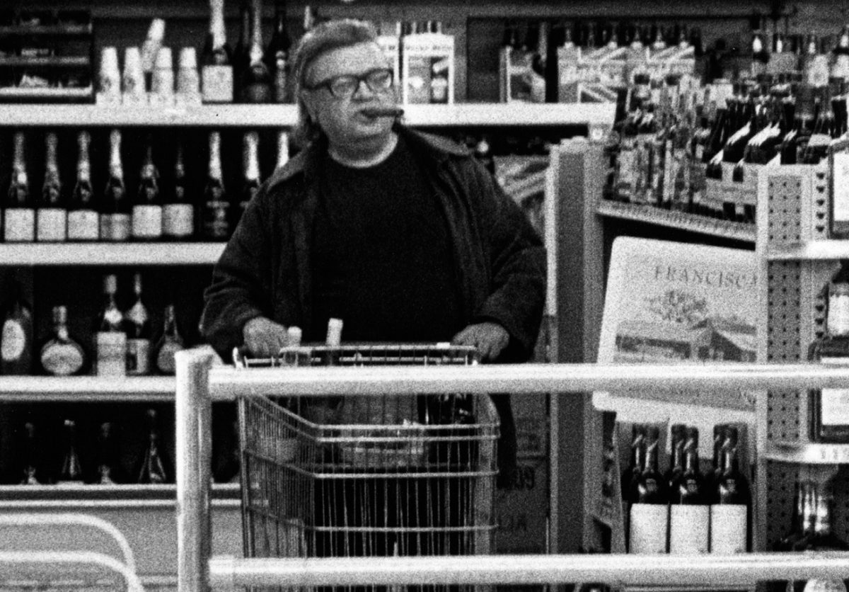 Mario Puzo, with cigar in his mouth, pushes a shopping cart through the aisles of a wine store.