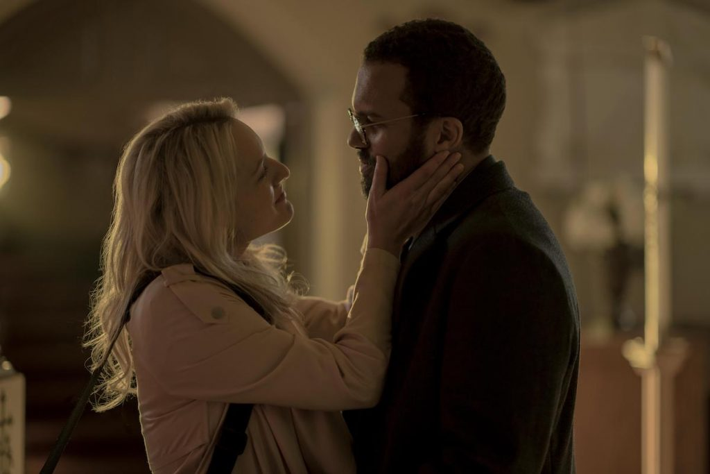 June (Elisabeth Moss) smiles and holds Luke's (O.T. Fagbenle) face between her hands in 'The Handmaid's Tale' Season 3. She wears a pink jacket and has a purse hanging over her shoulder and he wears a dark blazer and glasses.