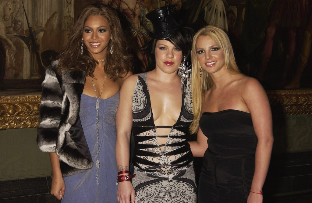 Beyonce Knowles, Pink, and Britney Spears pose together at an event smiling