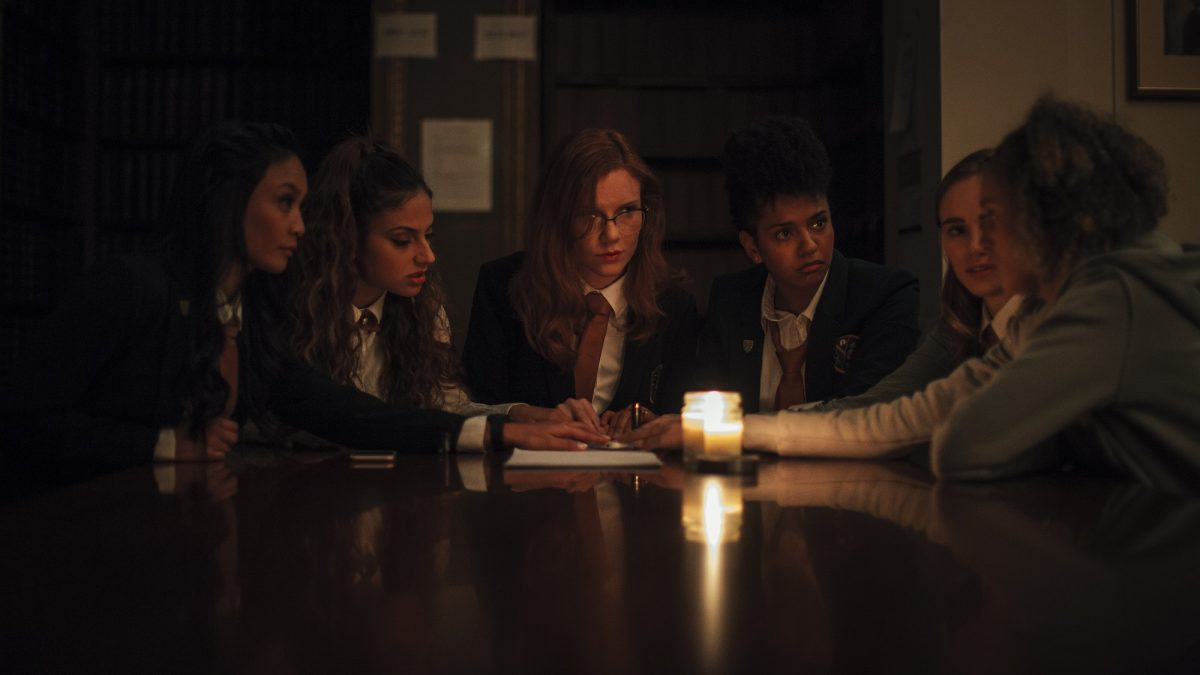 Seance cast plays with a Ouija board