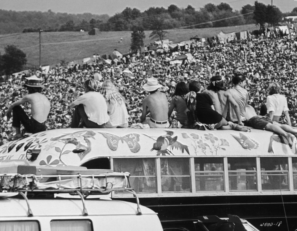 Fans sitting on top of a painted bus at the Woodstock Music Festival, 1969
