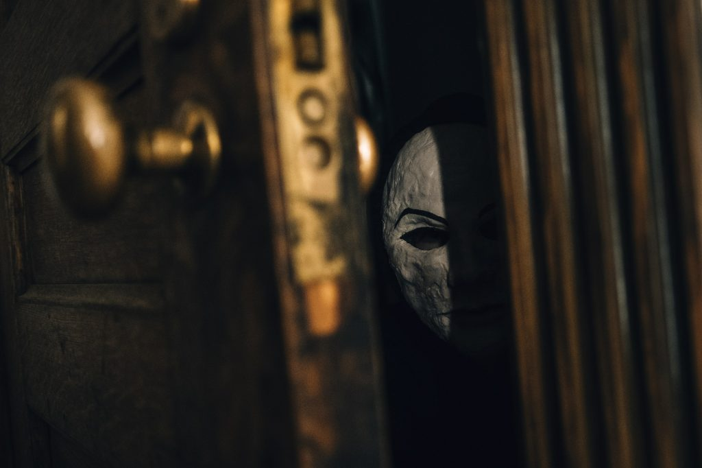 Seance mask peers through a crack in the door
