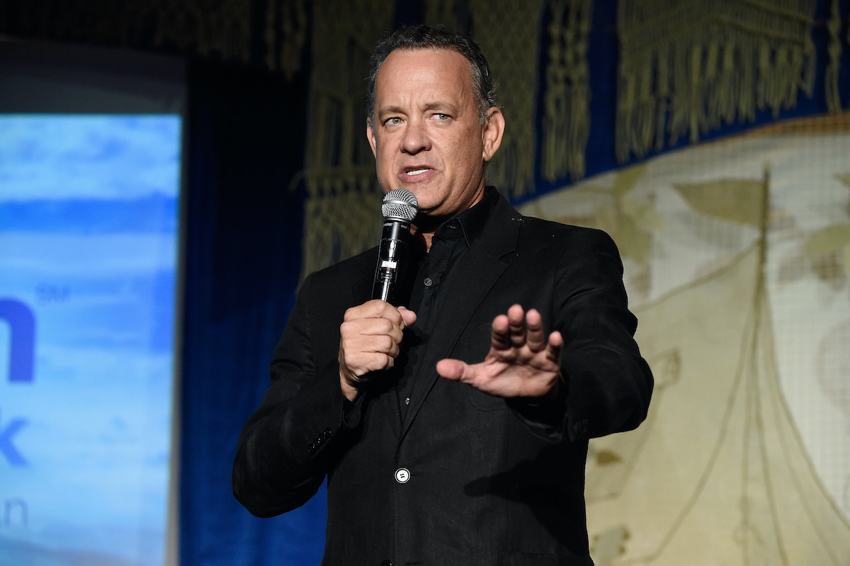 Tom Hanks holds a mic and looks serious while holding a hand out as he speaks onstage