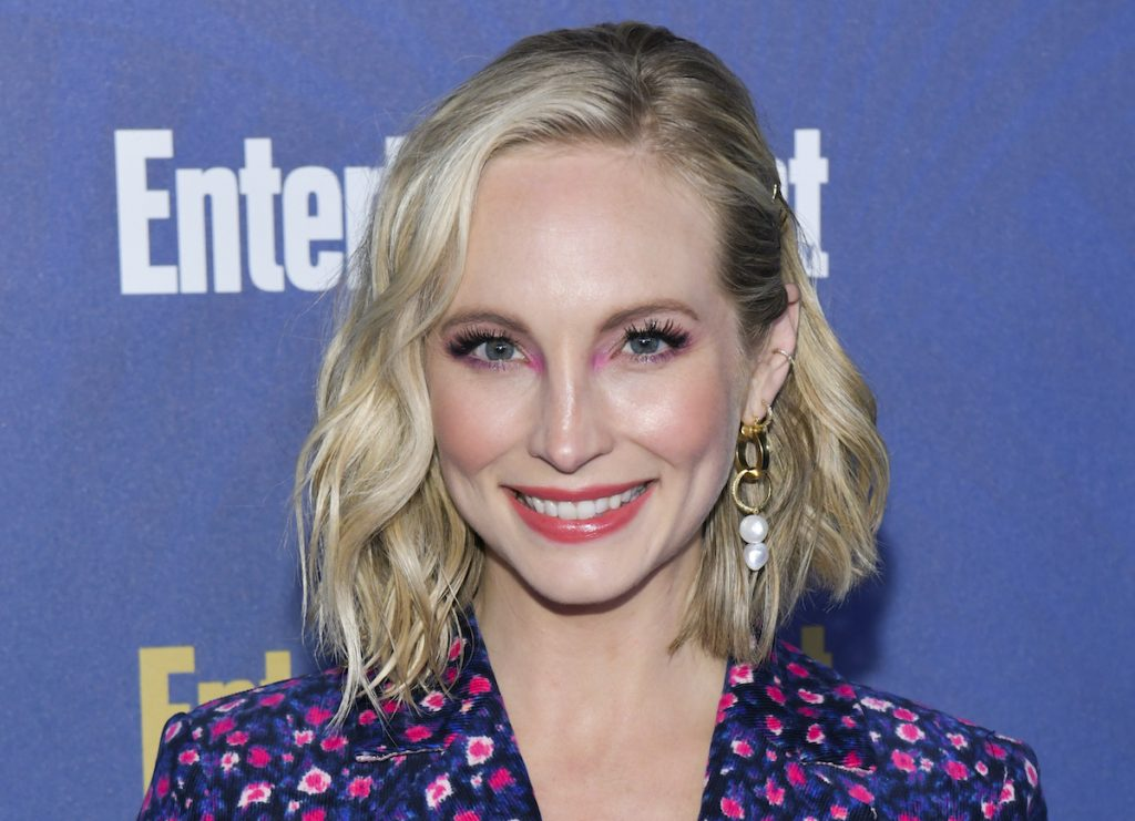 Candice King in a blue and pink floral suit smiling in front of a blue backdrop