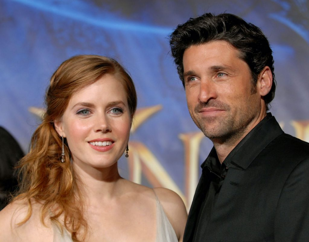 Amy Adams and Patrick Dempsey smile in front of a purple and blue backdrop that says 'Enchanted' in gold writing.