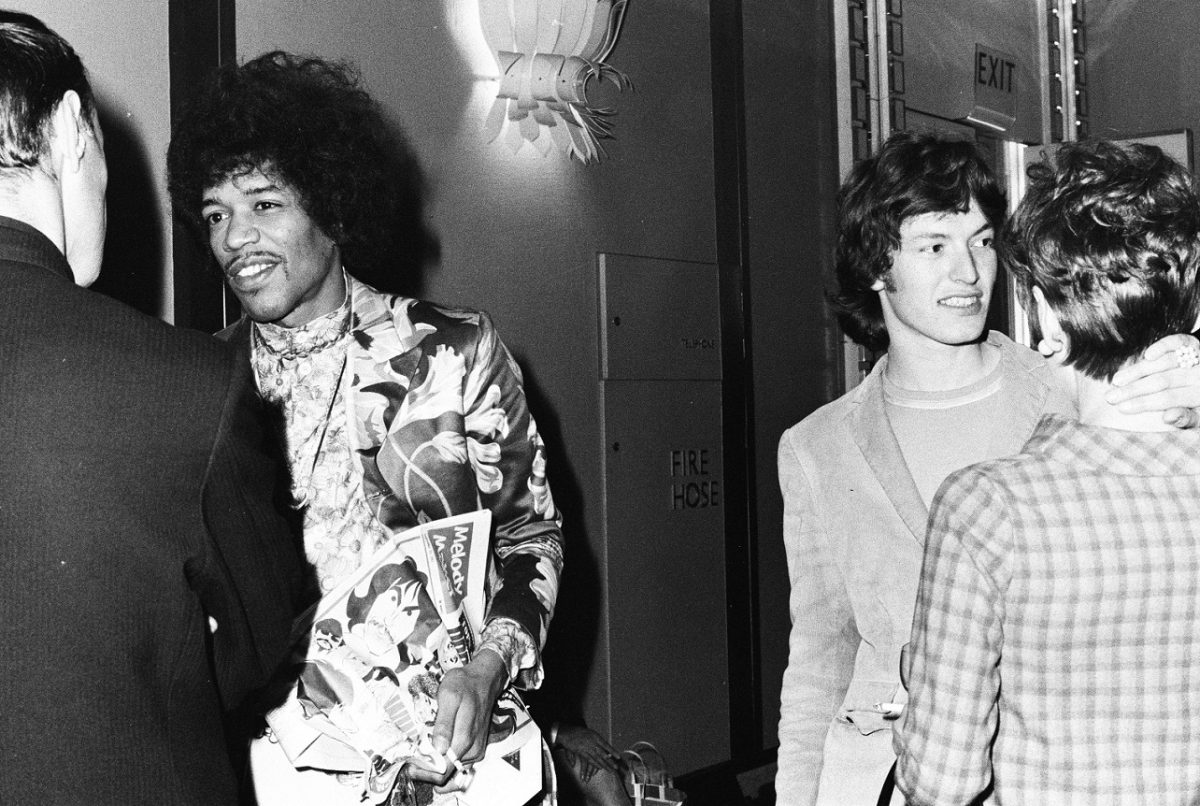 Jimi Hendrix and Steve Winwood smile as they talk with people at an award reception